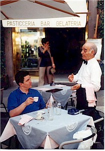 Frank enjoys un caffé and some reparteé with a waiter in Rome